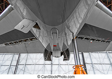 Auxiliary power plant in the tail of the aircraft with open hood covers, jack stand.