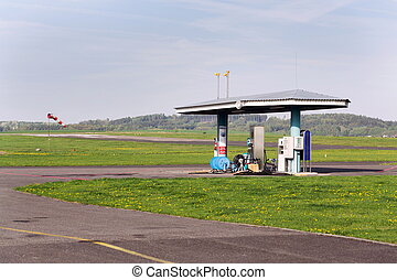 Aviation fuel filling station on airport with airfield runway in background on a sunny spring day