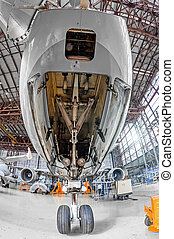 Aviation hangar with airplane, close-up front landing gear of the airplane landing gear on maintenance repair.