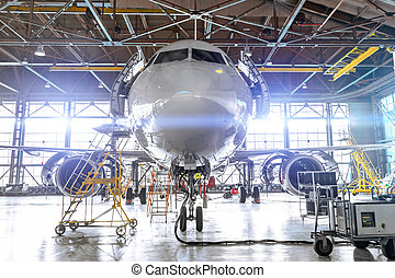Aviation hangar with passenger aircraft jet for maintenance. Bright lights lighting, glare.