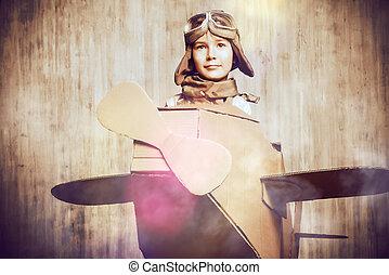 aviator - Cute dreamer boy playing with a cardboard...