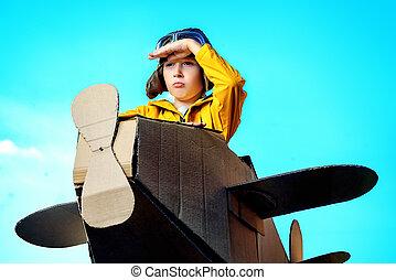 aviator - Eight-year boy playing with a cardboard airplane...