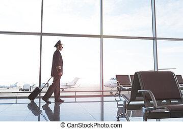 Aviator walking through waiting hall - Pilot wearing uniform...