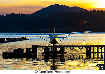 avion flotteur, à, dock, silhouetted, par, coucher soleil