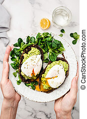 Avocado and poached egg on rye bread