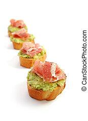 Avocado appetizer - Parma ham strips with avocado spread on...
