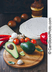 Avocado fruit on wooden board with other vegetables.