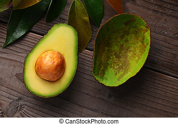 An Avocado cut in half on a wood surface with leaves. One half shows the seed while the other has been scooped out.