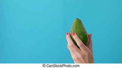 avocado in a hand of woman blue background