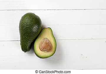 Avocado on a board painted with white paint