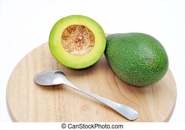 Avocado on the cutting board with spoon in a white background