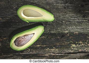 Avocado on wood. Dirrect sunlight