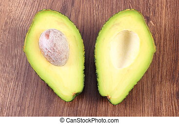 Avocado on wooden background, ingredient of avocado paste or guacamole, healthy food and nutrition
