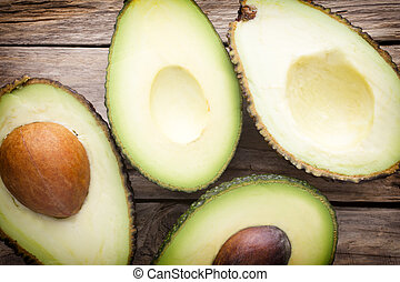 Avocado parts on the wooden table.