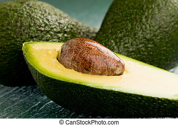 photo of cutted avocado fruit on green glass table