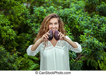 Pretty woman in white dress standing with avocado in hands