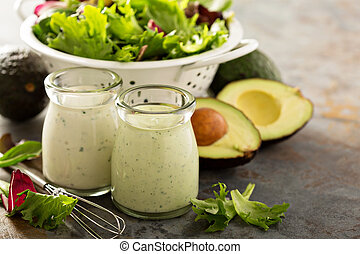 Avocado ranch dressing in small jar with salad leaves in a...