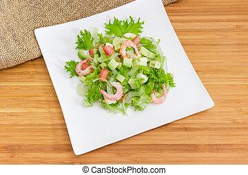 Avocado salad with mozzarella and shrimps on square dish