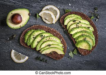 Avocado sandwich on dark rye bread made with fresh sliced...