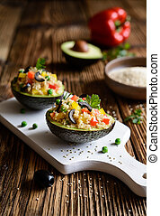 Avocado stuffed with quinoa, green peas, tomato, olives, bell pepper and parsley