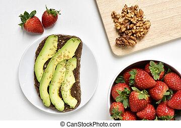 avocado toast, walnuts and strawberries - high-angle shot of...