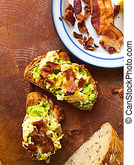 Avocado toast with eggs and bacon vertical