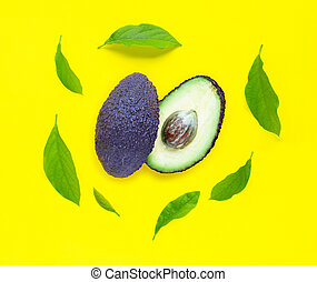 Avocado with leaves on yellow background.