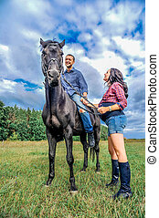 Awaiting the child, walking on the meadow. Young couple - she is a handsome brunette with long hair, pregnant; he is tall and brave, astride a beautiful black horse