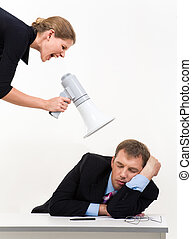 Portrait of businessman sleeping at workplace with businesswoman over him waking him up