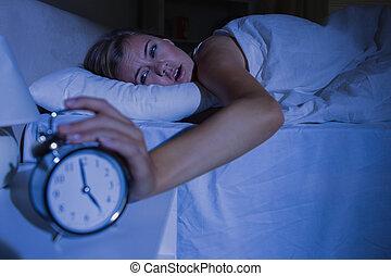 Awakening woman stopping her alarm clock