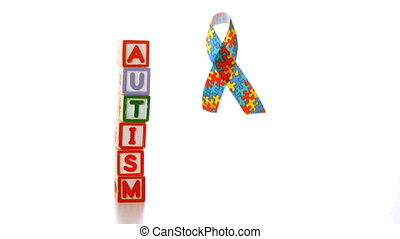 Awareness ribbon falling beside blocks spelling autism in...