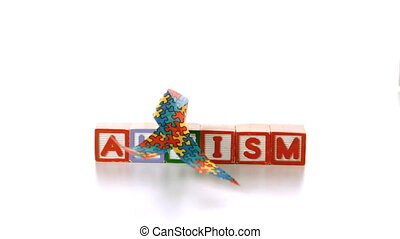 Awareness ribbon falling onto blocks spelling autism on...
