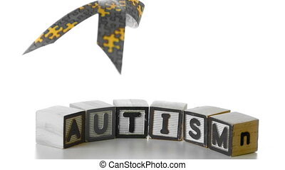 Awareness ribbon falling onto blocks spelling autism in slow...