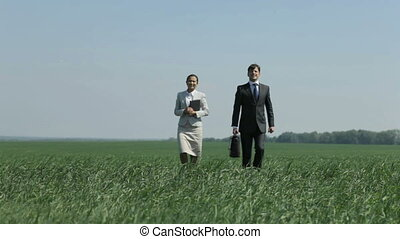Away - Positive business woman and her colleague strolling...