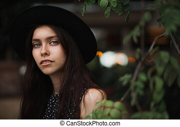 Awesome brunette girl wearing hat and vintage dress posing at the city street on a lights background. Space for text