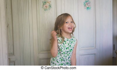 Awesome mood. Happy childhood. A pretty little girl is dancing and smiling. A little cute blondie is dancing and jumping in the bright room.
