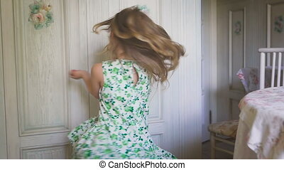 Awesome mood. Happy childhood. A pretty little girl is dancing and turning around. A little cute blondie is dancing and smiling in the bright room.
