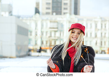 Awesome smiling blonde model wearing trendy cap having fun with sparklers at the street. Space for text