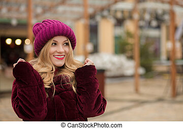Awesome smiling blonde woman with long lush hair posing at the street in in Kiev