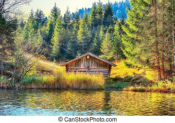 Awesome view of Wagenbruchsee (Geroldsee) lake with wooden hut and Karwendel mountains at early morning in autumn.
