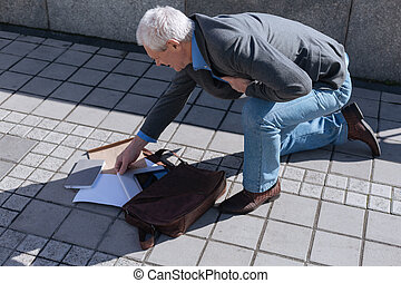 Awkward pensioner dropping bag from his hand outdoors