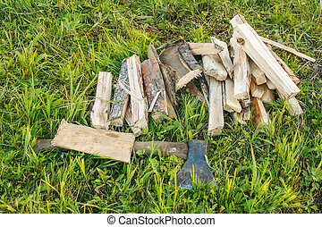ax and chopped firewood on the grass