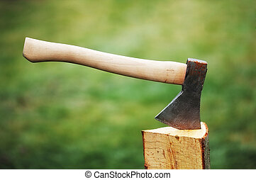 Axe in a log on the background of green grass