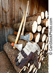 Axe, protective gloves and stack of logs - Heavy axe and a...