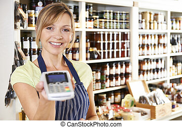 ayudante ventas, en, almacén del alimento, con, máquina tarjeta crédito