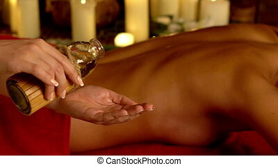 Ayurveda massage therapy with holistic treatment in spa with burning candles. Slow motion close-up of masseuse's hands into which massage oil is poured on background of female body wearing in towel.