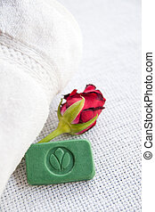 Stilllife with ayurvedic herbal soap with cachet Green Leaf, red rose and towel