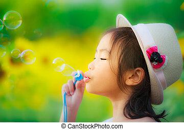 aziaat, klein meisje, is, blazen, een, de bellen van de zeep, in, zonnebloem, tuin