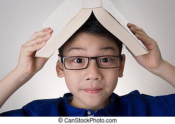 aziatische jongen, met, boek, op, hoofd, denken