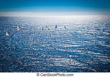 Azur blue sea with sailboats in sunset.
